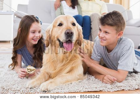 Siblings lying with dog while mother and father sitting on sofa at home