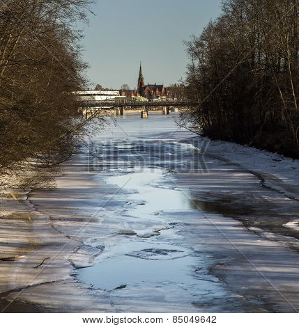 Thawing River With Distant Church