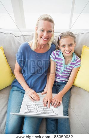 High angle portrait of happy mother and daughter using laptop on sofa at home
