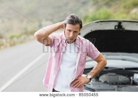 Stressed man waiting assistance after a car breakdown at the side of the road