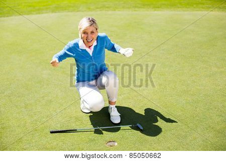 Excited lady golfer cheering on putting green on a sunny day at the golf course