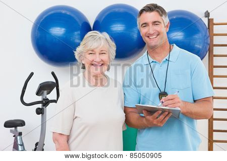 Senior woman and trainer smiling at camera in fitness studio