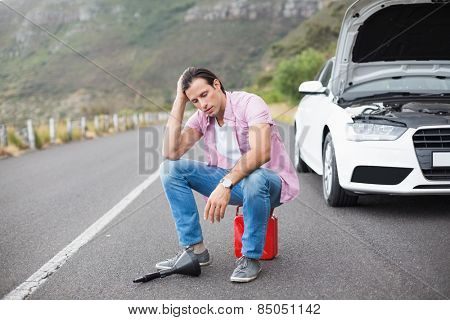 Stressed man after a car breakdown at the side of the road