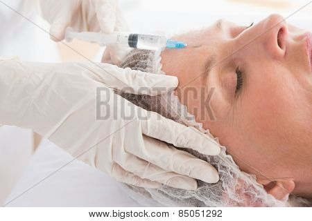 Woman receiving botox injection on her forehead in medical office