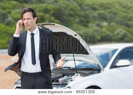Businessman after a car breakdown at the side of the road