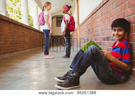 Portrait of smiling schoolboy with friends in background at school corridor