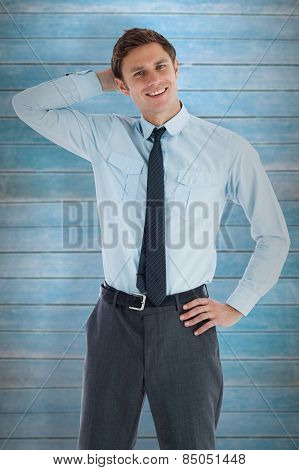 Thoughtful businessman with hand on head against wooden planks