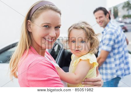 Parents carrying baby and her car seat out of the car
