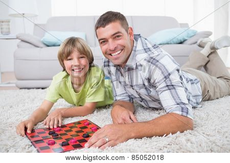 Portrait of happy father and son playing checker game while lying on fur at home