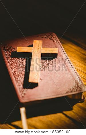 Crucifix icon resting on the bible on wooden table
