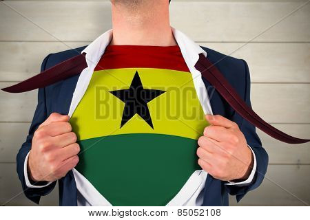 Businessman opening shirt to reveal ghana flag against bleached wooden planks background