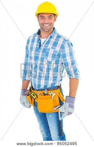 Portrait of smiling handyman wearing tool belt on white background