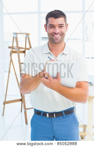 Portrait of smiling male handyman writing on clipboard at construction site