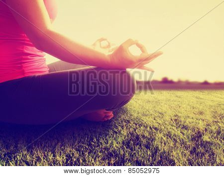 hands of a woman meditating in a yoga pose on the grass toned with a retro vintage instagram filter app or action effect