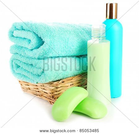 Towels in wicker basket with shampoo bottles and soap isolated on white