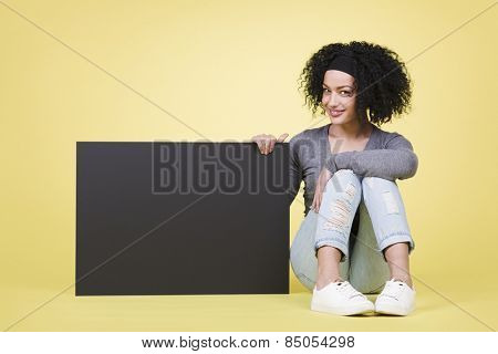 Smiling young woman being joyful  holding a black paper sign board with copy space.