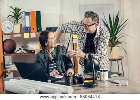 Two hipster managers working on laptop. Small Business Owner.