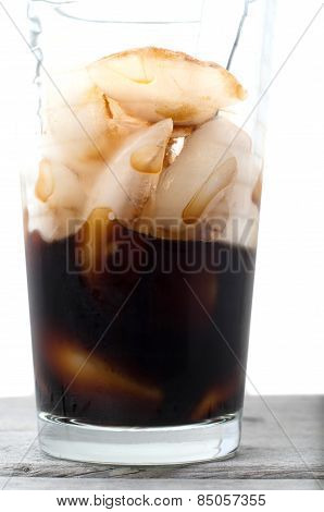 Half Empty Vietnamese Ice Coffee Glass On A Wooden Table Against White Background