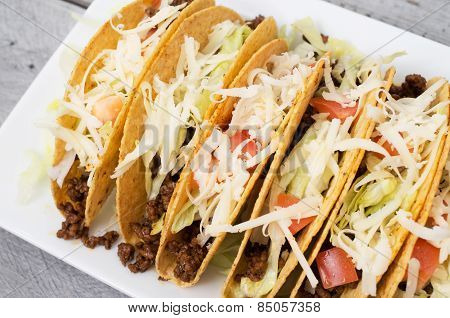 Ground Beef Tacos With Cheese Lettuce And Tomatoes Against Wooden Background