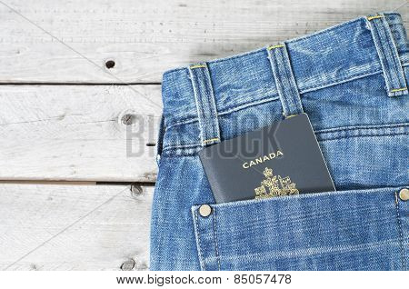 Canadian Passport In Blue Jeans Back Pocket Against Wooden Background