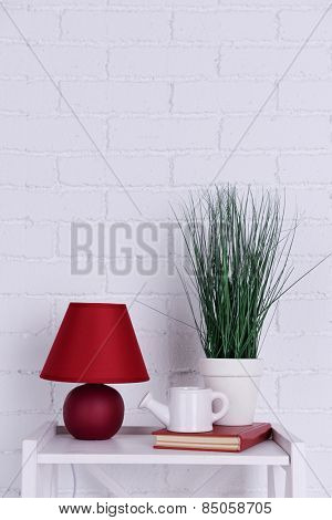 Interior design with lamp, plant, ceramic watering pot and book on tabletop on white brick wall background