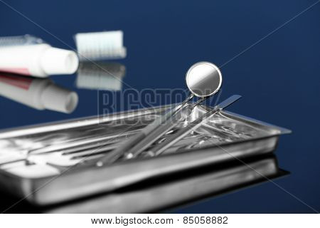 Dentist tools in metal tray with toothpaste and brush on blue background