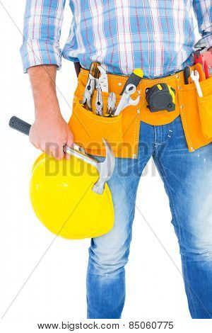 Midsection of manual worker wearing tool belt while holding hardhat and hammer on white background