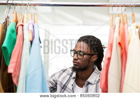 Portrait of male fashion designer looking at rack of clothes