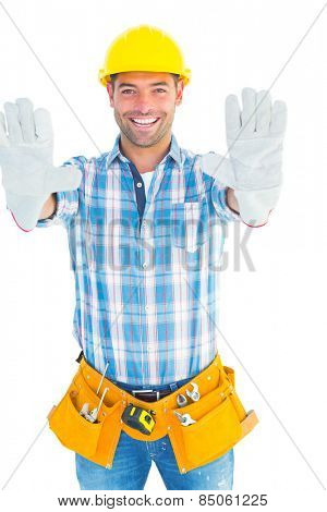 Portrait of happy manual worker making stop sign on white background