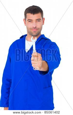 Portrait of confident male mechanic showing spanner on white background