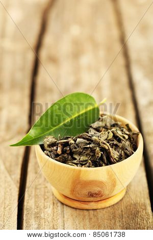 Green tea with leaf in bowl on old wooden table