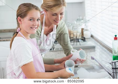 Happy mother and daughter washing up together at home in the kitchen
