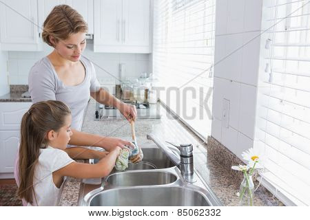 Mother and daughter washing up at home in kitchen