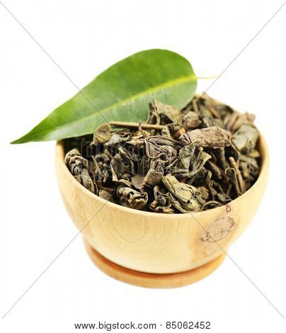 Wooden bowl with green tea with leaf isolated on white