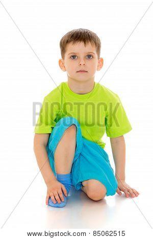 little boy sat down on one leg