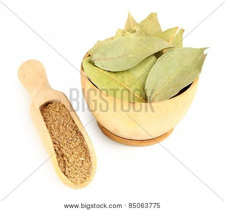 Bay leaves in wooden bowl, isolated on white