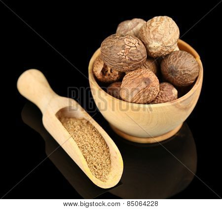 Nutmeg in wooden bowl, isolated on black