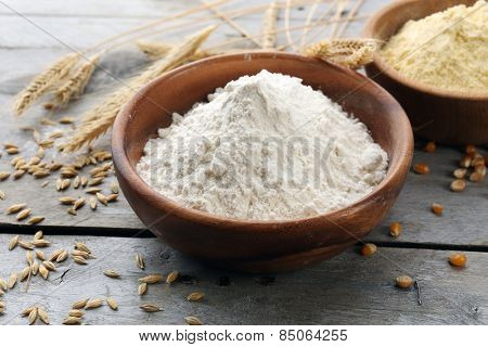 Flour in bowls with grains on wooden background