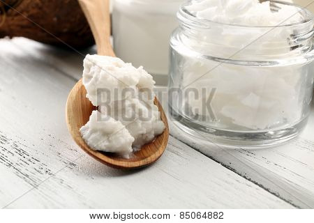 Coconut with jars of coconut oil and cosmetic cream on table close up