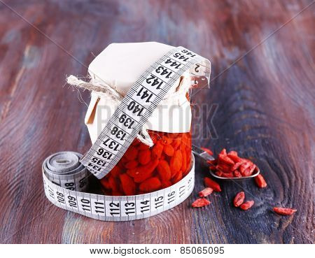 Goji berries in glass bottle wrapped with paper with measuring tape on wooden table background