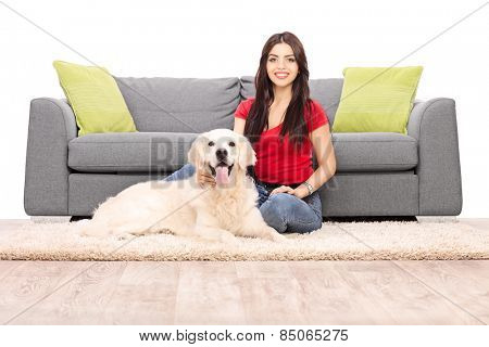 Young woman sitting by a sofa with her dog isolated on white background