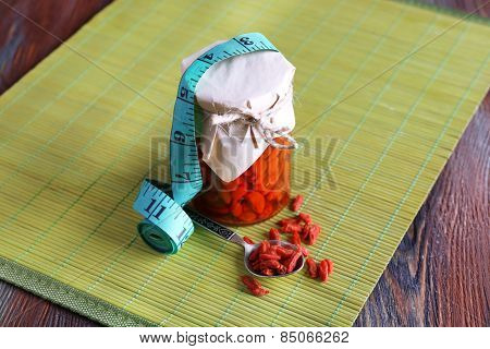 Goji berries in glass bottle wrapped with paper on bamboo mat with measuring tape on wooden table background