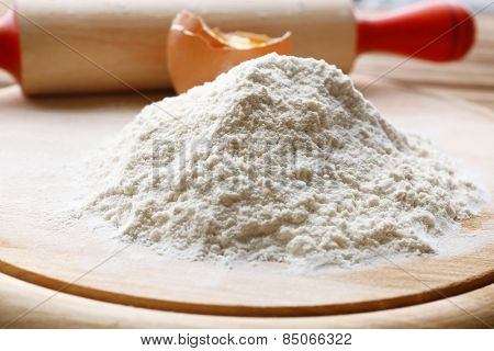 Heap of flour on cutting board with egg and plunger on wooden table