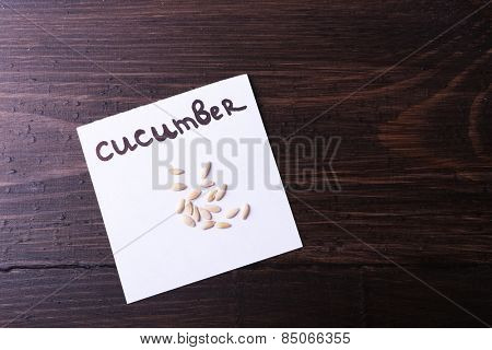 Cucumber seeds on piece of paper on wooden background