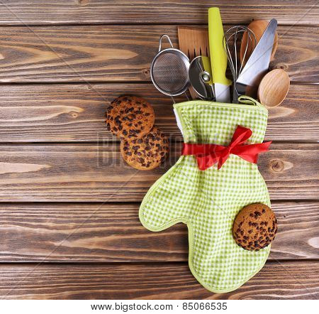 Set of kitchen utensils in mitten with chocolate cookie on wooden planks background