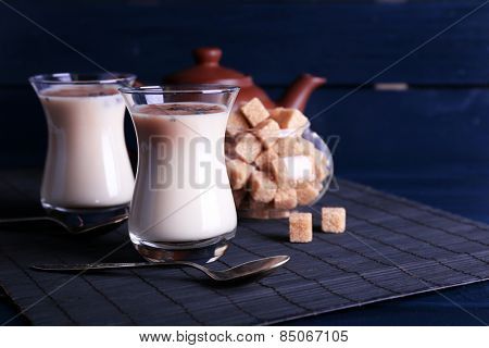 Black tea with milk in glasses and teapot with lump sugar on bamboo mat and color wooden planks background