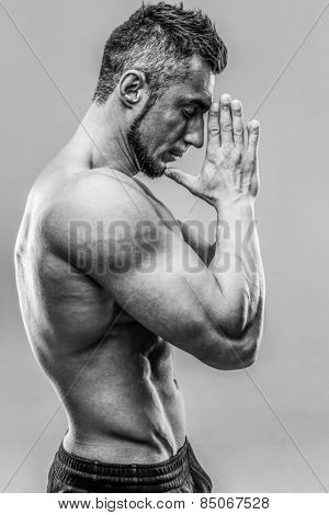 Portrait of a muscular man keeping his palms by face. HDR monochrome.