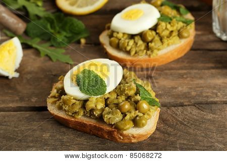 Sandwiches with green peas paste and boiled egg on rustic wooden planks background