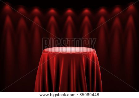 Round presentation pedestal covered with a red silk cloth in front of a wall illuminated by spot lights