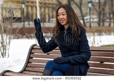 smiling Asian girl on a Park bench waving